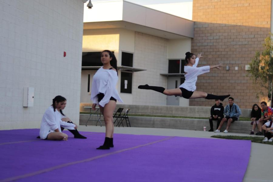 Sophomore Alene Hata opens up the dance with a leap as Jaylin Moreno stands from her opening pose.