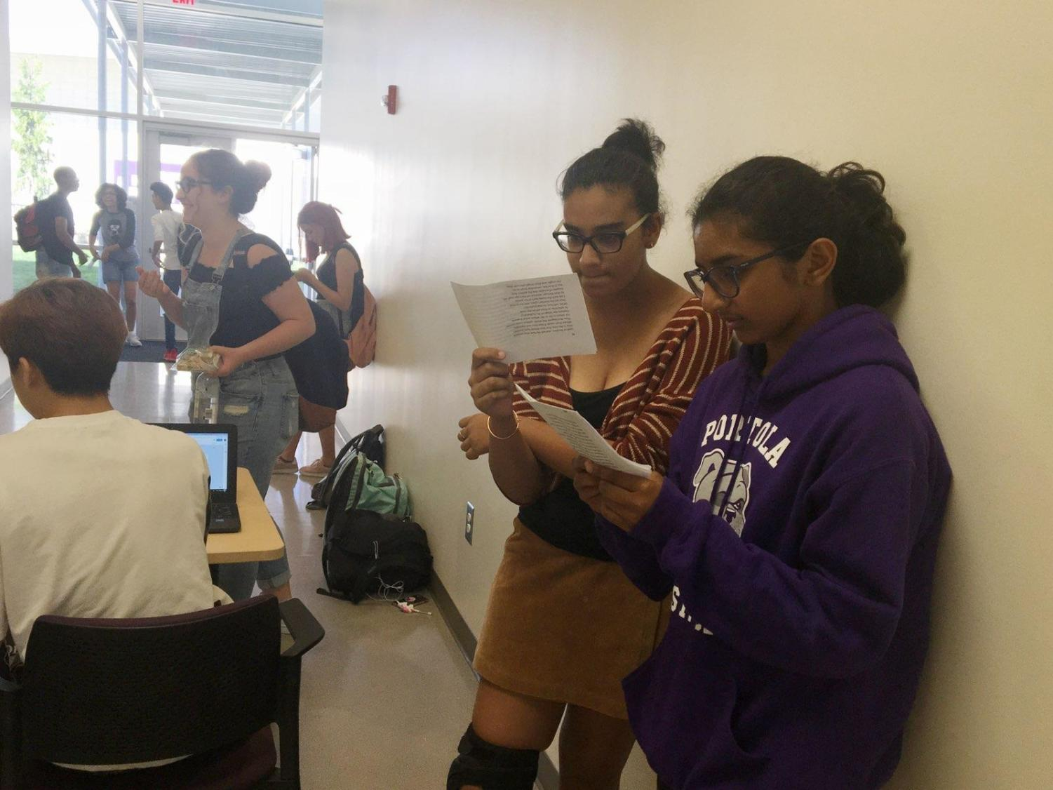 Freshmen Zara Shirwany and Naria Alam intently study their lines outside the theater doors as they wait for their auditions.