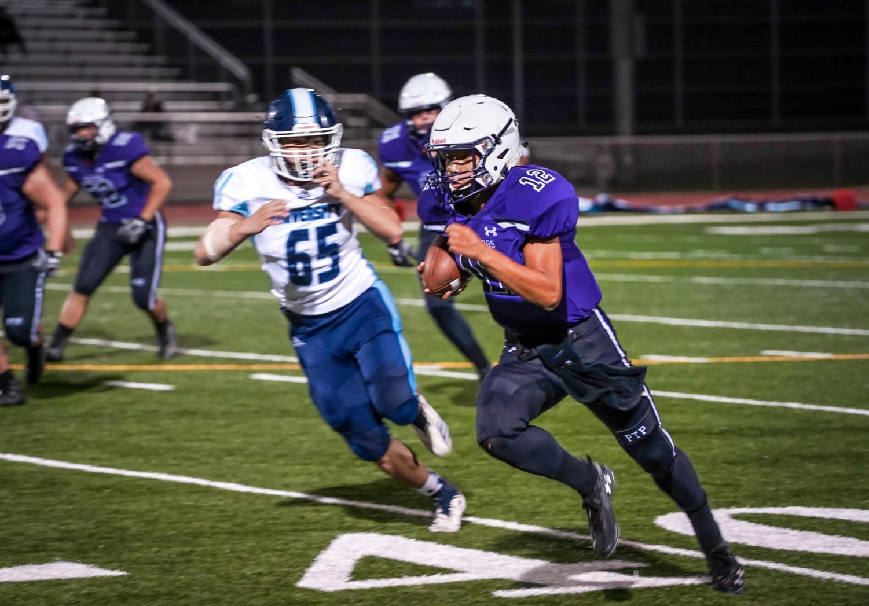 Quarterback Brandon Yue rushes the ball against the Trojans.