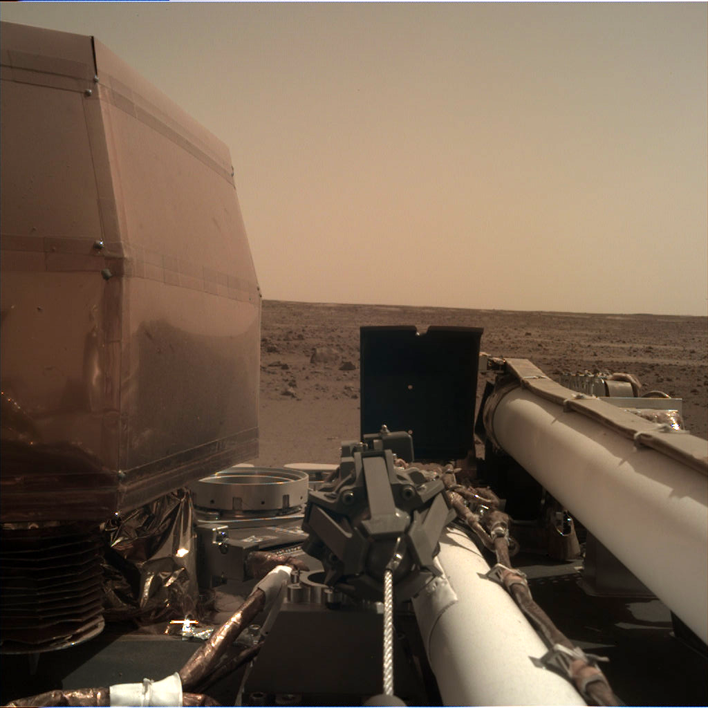 Insight lands and takes a picture using its Instrument Deployment Camera (IDC) from the surface of Mars.