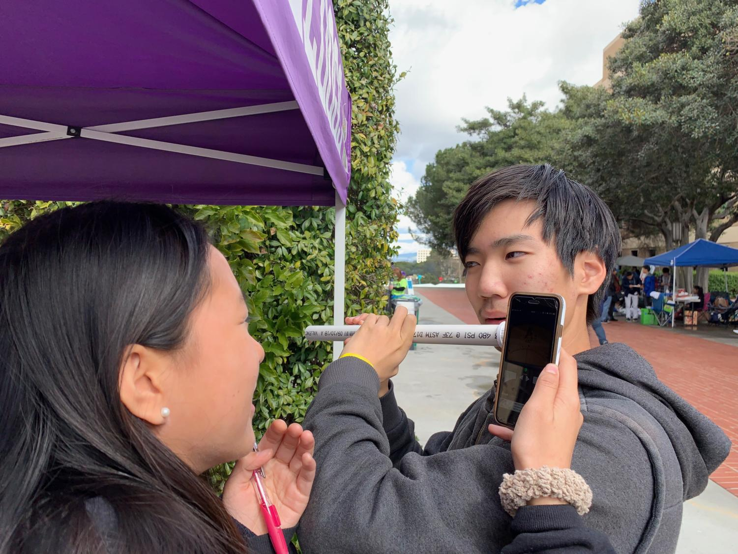 Junior Yunseong Jung tests out the flute that he and partner junior Stephanie Zhang built to compete in the event Sounds of Music. In the event, team members play the twelve tone scale on the flute they constructed, with pitch frequency being tested for accuracy.