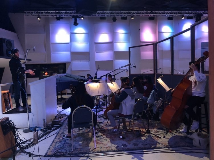 Music teacher Desmond Stevens conducts the members of the orchestra as they record in the studio. In studio recordings, the musicians have to both follow the conductor and listen in the headphones for the metronome and cues.