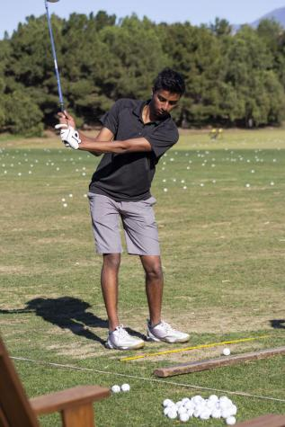 Sophomore Kevin Lu carefully and determinendly putts the ball with the hole in sight. With a focus on minimizing the overall score, even a slight error on one shot can drastically affect team performance.