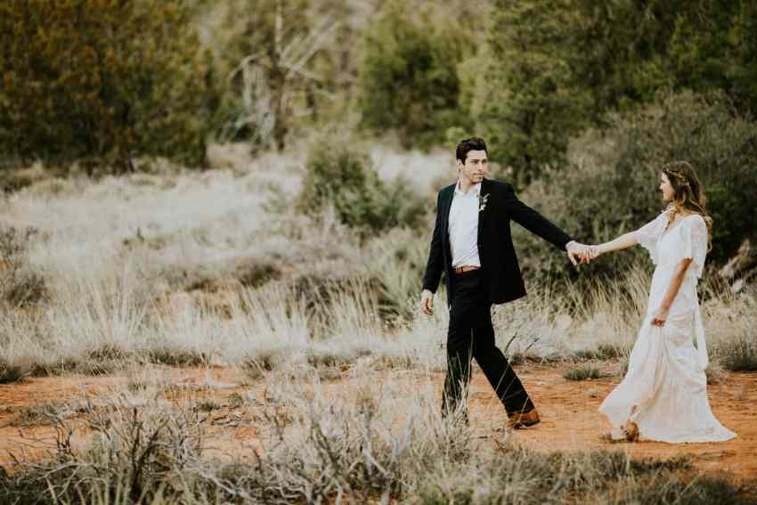 groom leading bride in sedona desert