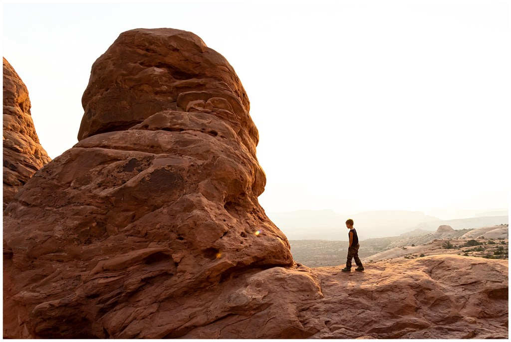 young boy walking at arches national park
