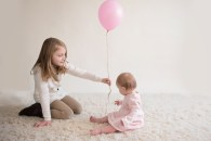 sister helping little sister with balloon