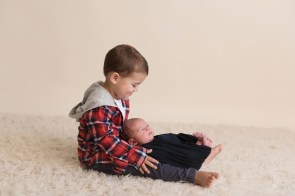 big brother holding new baby in lap