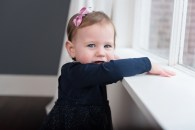 baby girl standing at window
