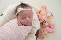newborn girl with floral backdrop