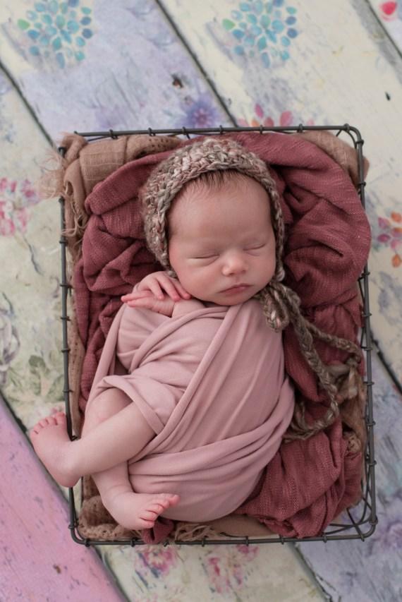 newborn in wire basket in bonnet