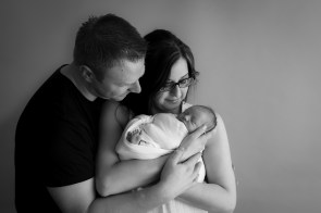 parents black and white looking at baby