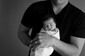 baby wrapped in daddys arms