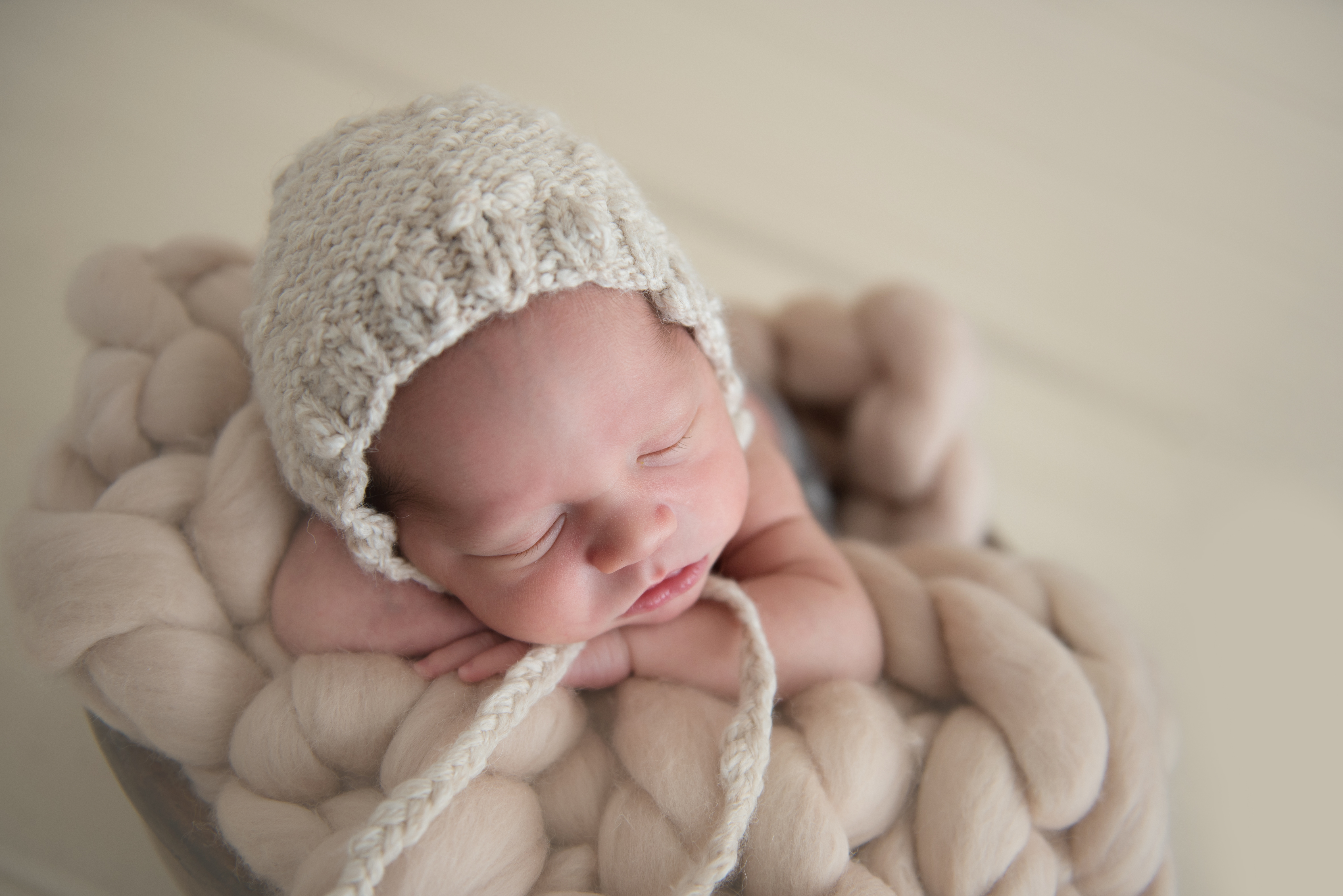 baby on belly wearing cotton bonnet