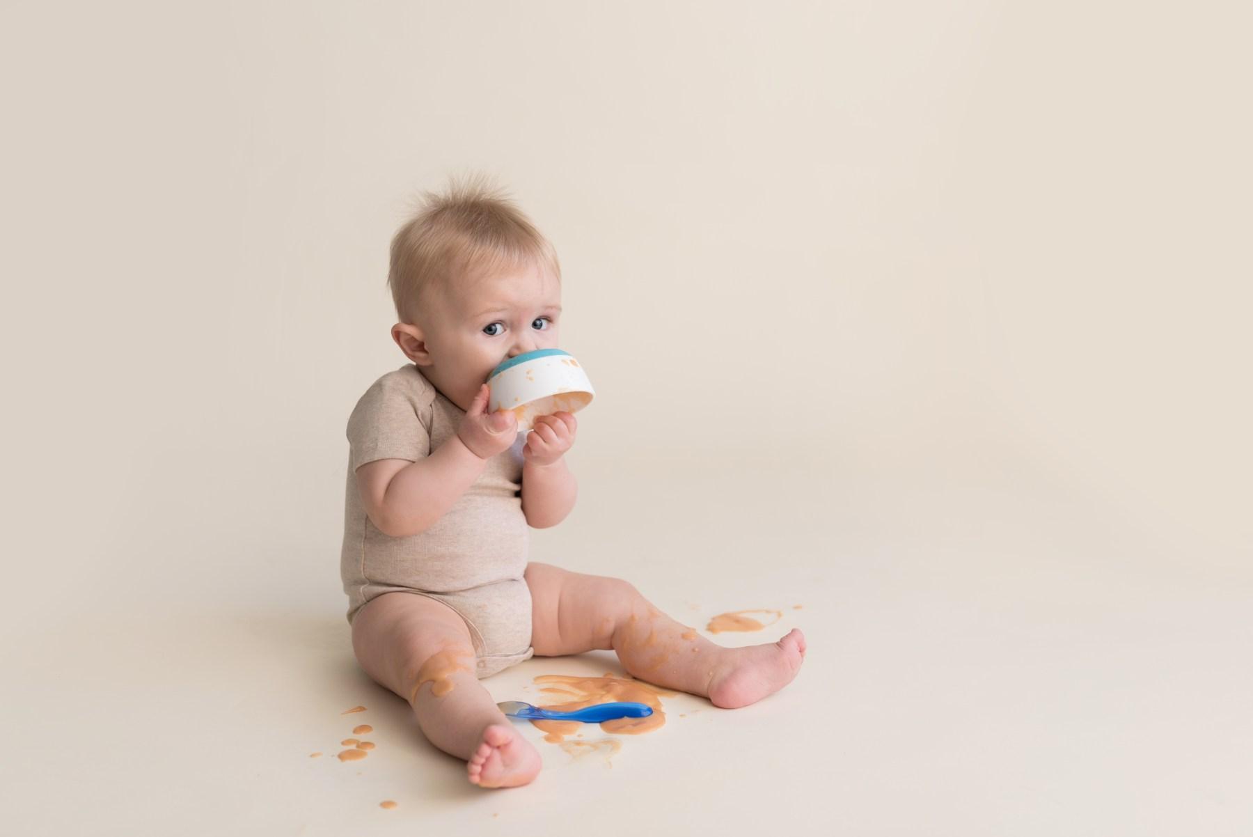 sitter boy feeding himself with spoon