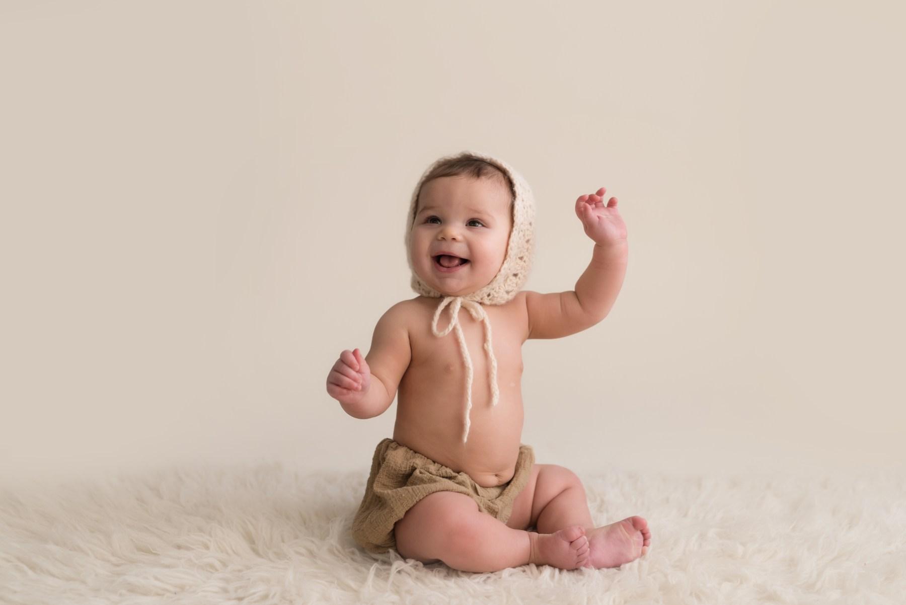 baby sitting in bonnet neutral bone tan