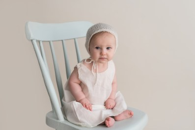 vintage baby in dress sitting in chair
