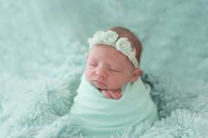 baby girl wrapped in mint potato sack