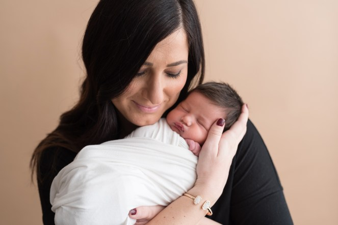 baby in white wrap in moms arms