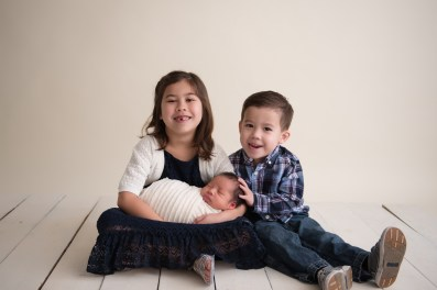 siblings holding new baby