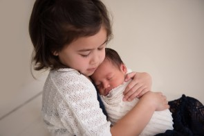 sisters snuggle with new baby