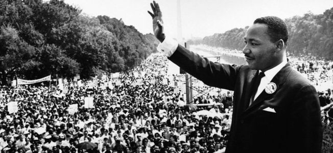 Martin Luther King waving at crowd. Black and white photo.