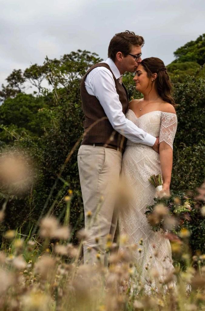 Bride & groom kissing in field of flowers