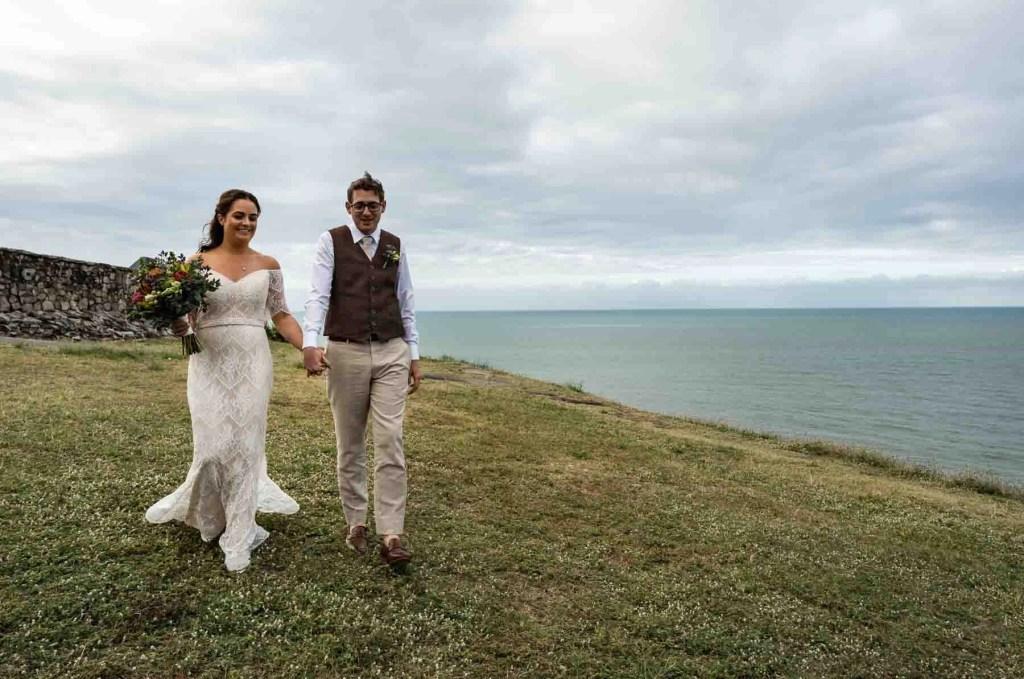 Bride & groom walking with stunning great barrier reef backdrop