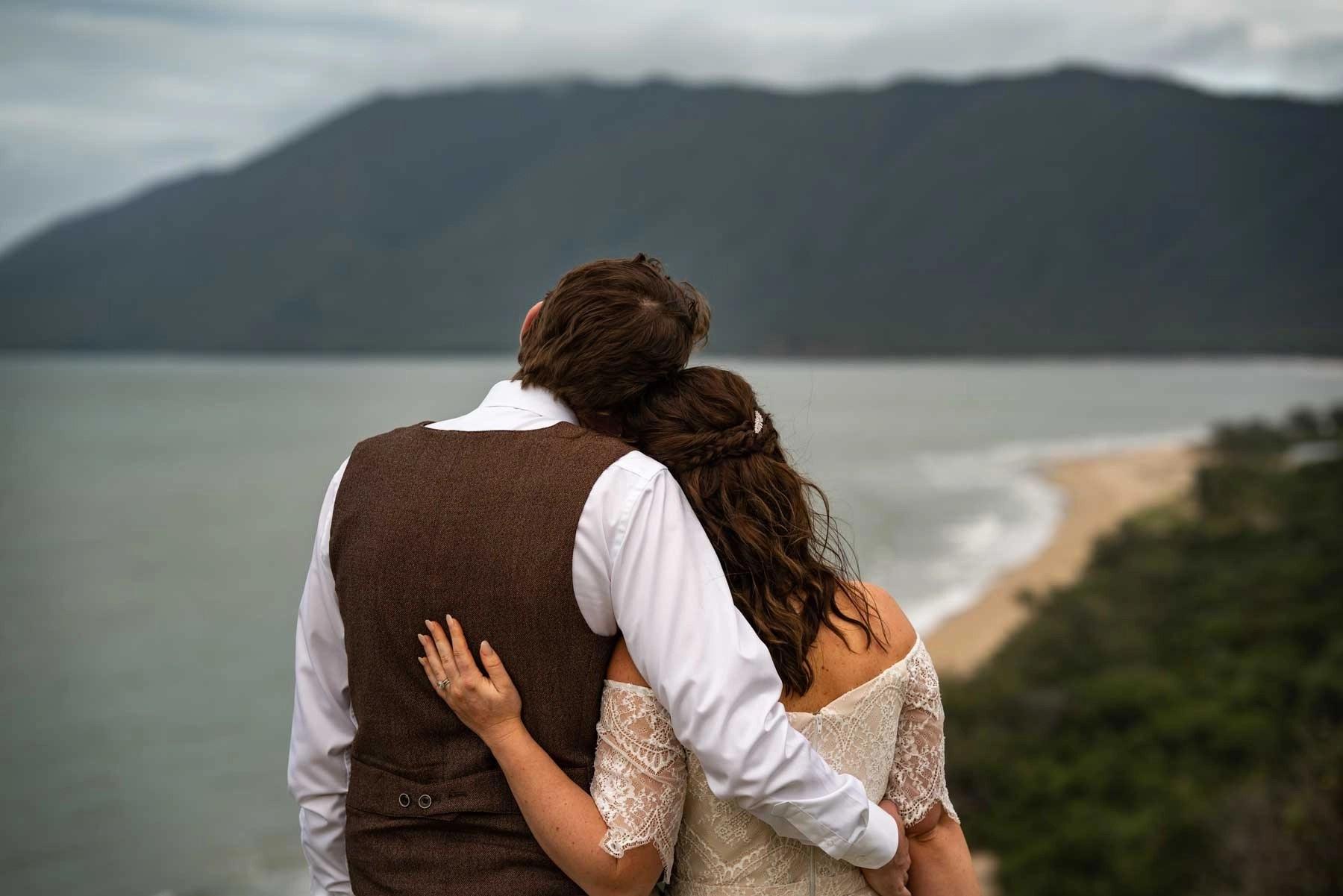 Bride & groom looking out across beach landscape