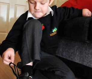 Our little hero: Boy, eight, overcomes amputation to play computer games and tie shoelaces one-handed
