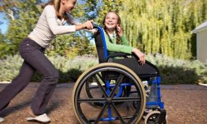 Smiling girl in wheelchair pushed by another girl