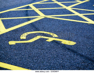 the-yellow-road-markings-of-a-disabled-parking-bay-on-a-tarmac-road-ew3nfp