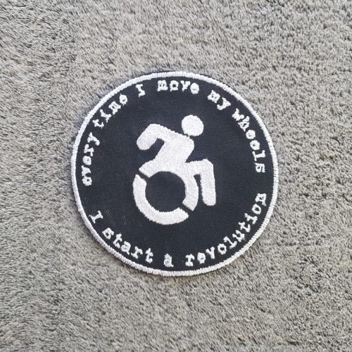 "A round black patch with a wheelchair user in the centre. Around it, the text reads ""when I move my wheels I start a revolution"""