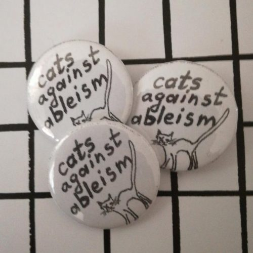 "Three black and white badges on a checked black and white backdrop. They each feature a drawing of a cat and read ""cats against ableism""."