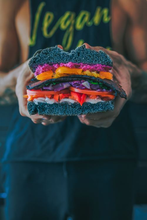 A person holding a large, colourful vegan sandwich