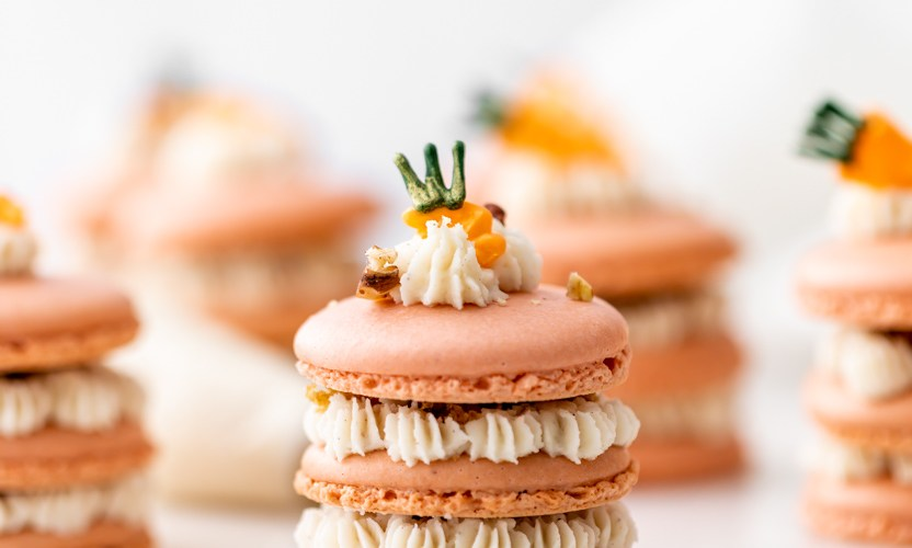 Carrot cake macaron stacks made with cinnamon frosting and carrot cake filling. Decorated with carrot icing decorations. Dairy & Gluten Free and perfect for Easter dessert menus!
