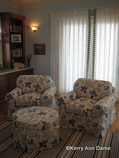 A pair of blue and white slipcovered floral chairs share a round ottoman on wheels