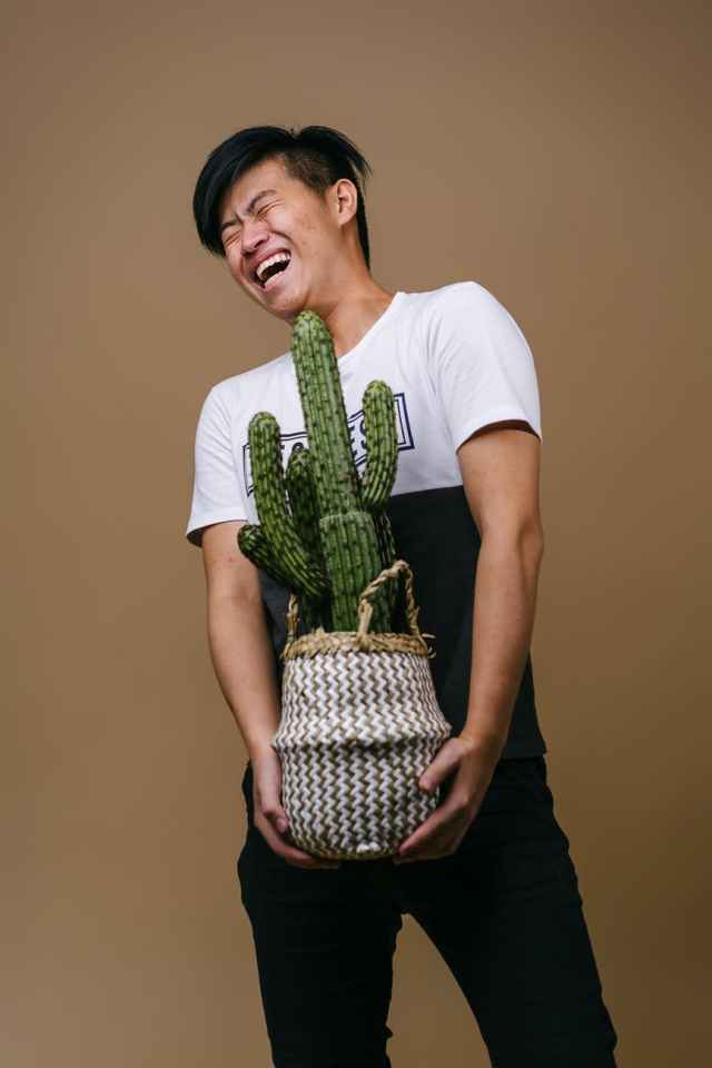 man in white and black shirt holding pot with cactus plant