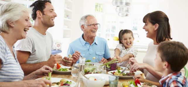 Multi generation family eating meal laughing around kitchen table_dietitian angela hubbard