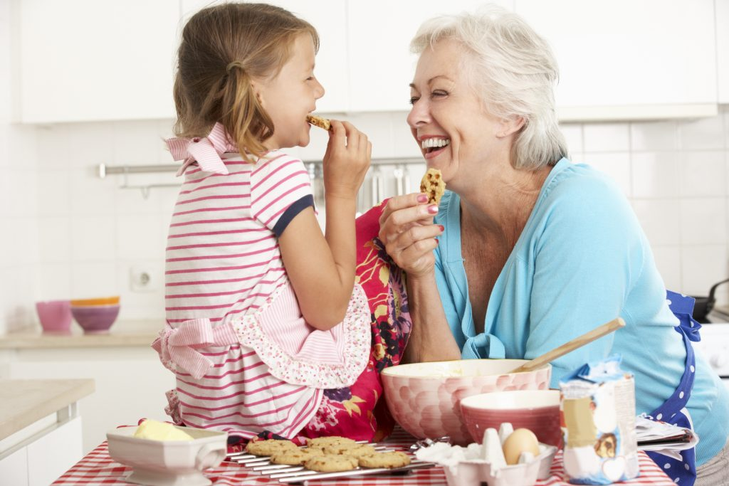 grandmother and granddaughter smiling and eating fresh baked cookies_dietitian angela hubbard