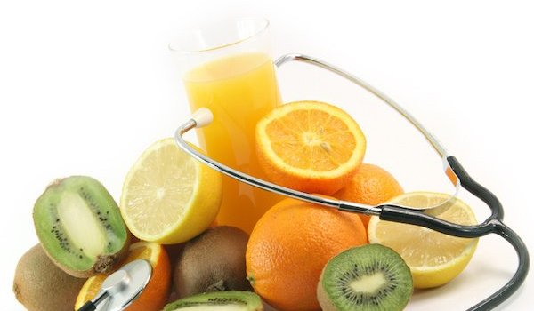 pile of citrus fruit and juice with stethoscope dietitian vs nutritionist food as medicine