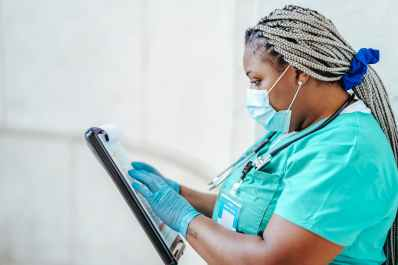 black physician reading document on clipboard at work