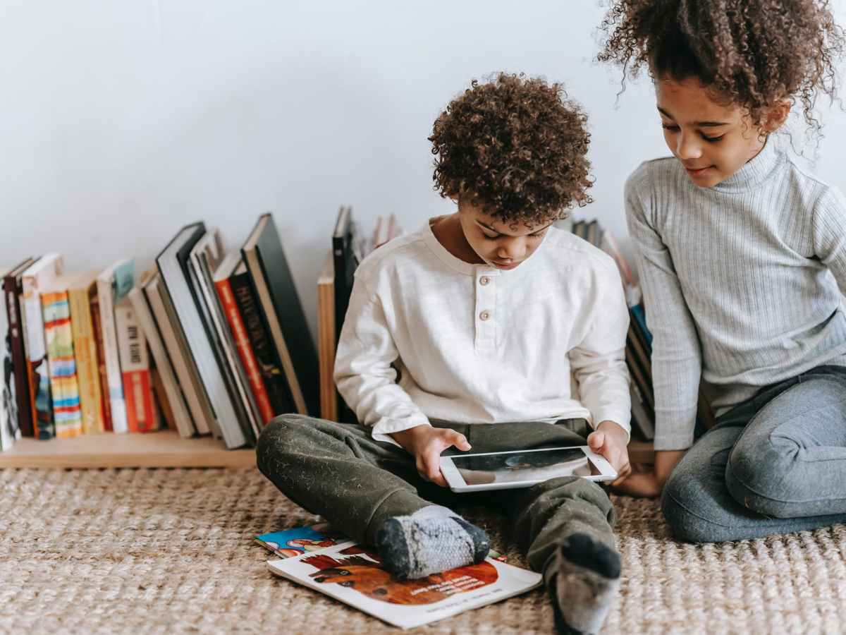 focused black children with tablet in room