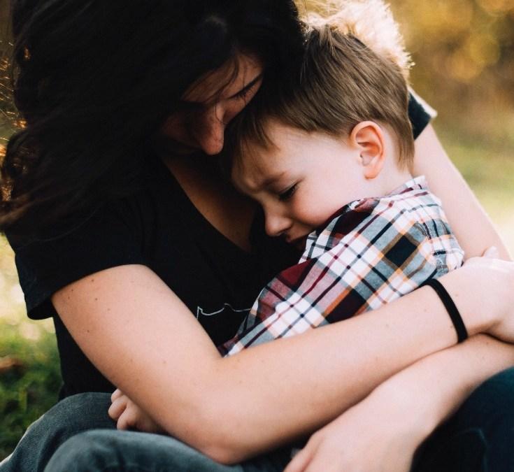 Mum cuddling boy - positivespecialneedsparenting.com