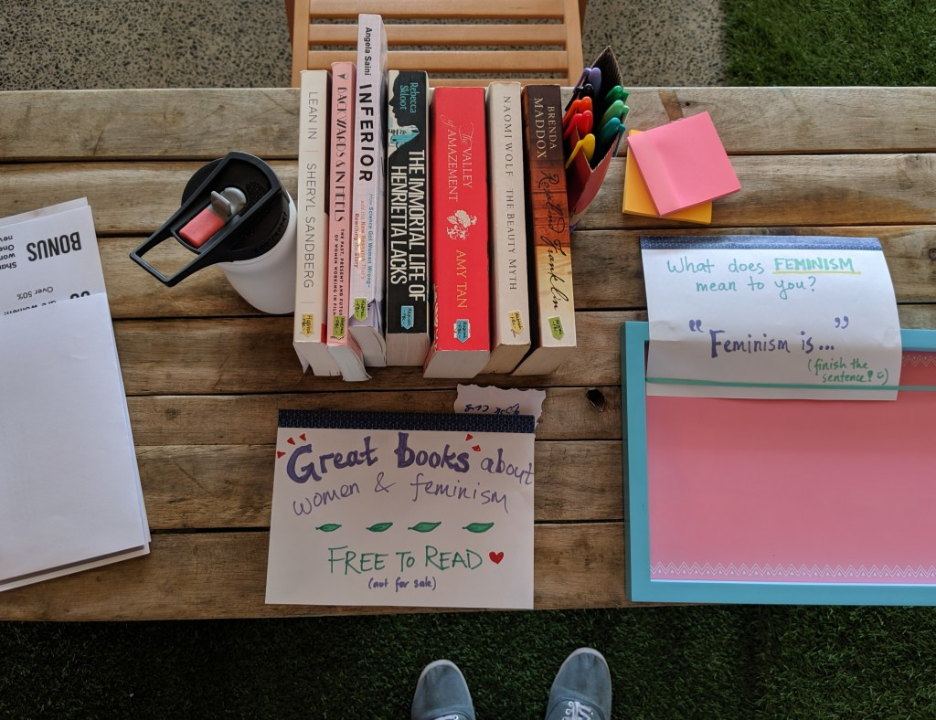 "Picture of a table with a small number of books on it, a sign ""Great books about women & feminism - free to read"", some stationery, and an empty board with a sign ""What does feminism mean to you?"""