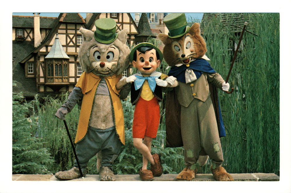 """Watch out Pinocchio! Pinocchio relaxes with his two """"friends,"""" Foulfellow and Gideon in fantasyland. This is the happiest land of them all, where guests me dozens of famous characters """"come to life"""" from Disney animated film classics."""