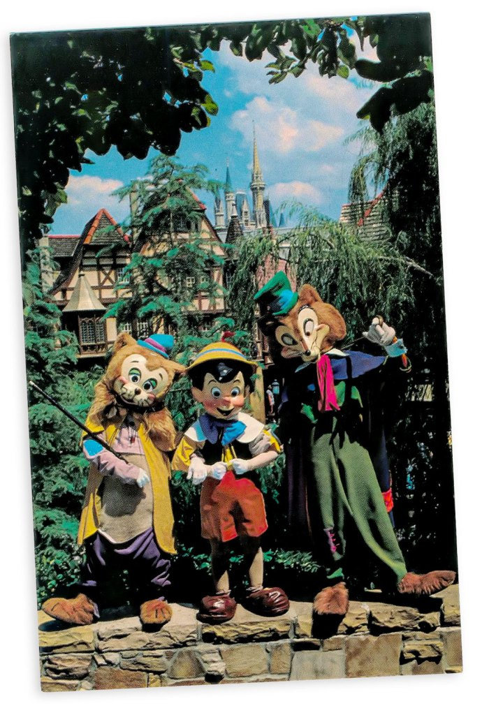 "Watch out Pinocchio! (Postcard)  Pinocchio relaxes with his two ""friends"" Foulfellow and Gideon in Fantasyland. This is the happiest land of them all, where guests meet dozens of famous characters ""come to life"" from Disney animated film classics."