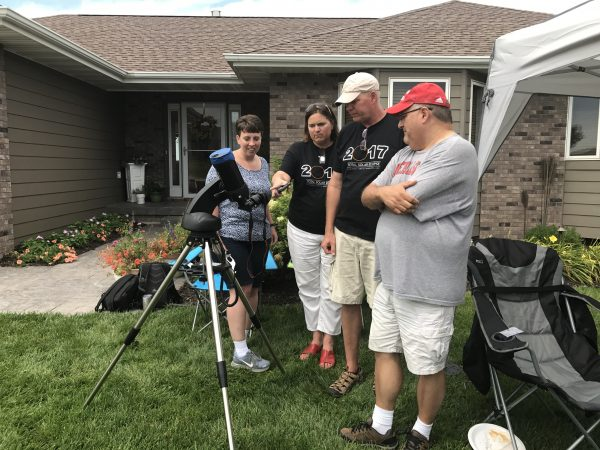 Friends and fellow travel bloggers look at the eclipse through a telescope in our front yard.