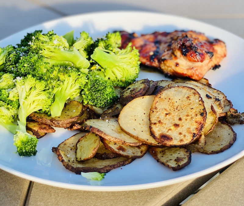 sliced potatoes on the grill with chicken
