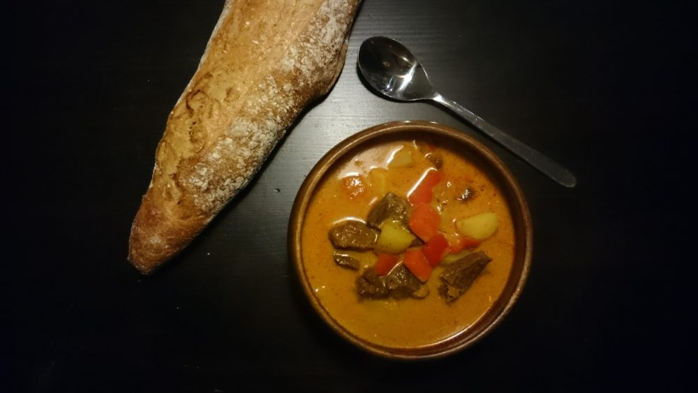 Bowl of goulash and a homemade flute