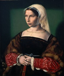 Anne Stafford wears a black fur-lined gown with turned-back sleeves over a dark kirtle. She wears a soft sash at her waist and a sheer partlet over a square-necked chemise, c. 1535.